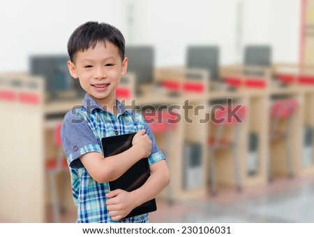 Asian boy with tablet computer in school library smiling