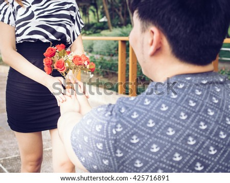 Asian Boyfriend offering his girlfriend a bunch of roses in the park. - stock photo