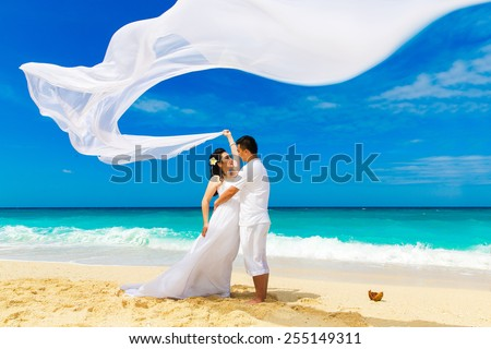 Asian bride and groom on a tropical beach. Wedding and honeymoon concept. - stock photo