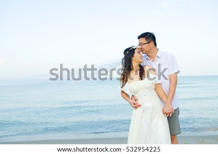 Asian bride and groom on a tropical beach. Wedding and honeymoon concept.