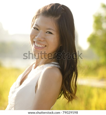 Asian bride at outdoor in a morning surrounding by golden sunlight - stock photo