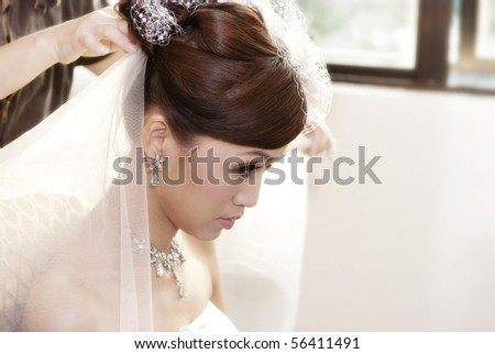 Asian bride having hairdo on her wedding day - stock photo