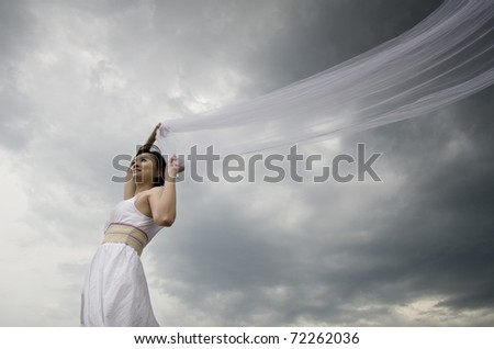 asian bride holding veils with wind blowing - stock photo