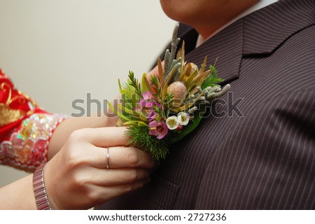 asian bride putting corsage on groom's jacket - stock photo