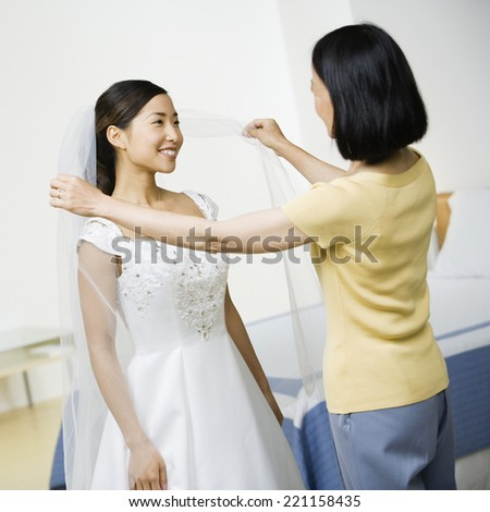 Asian bride smiling at mother - stock photo