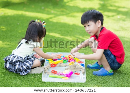asian brother and sister play sand - stock photo