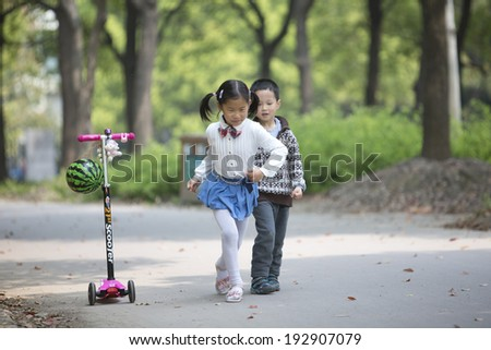 Asian brother and sister running in the park happily
