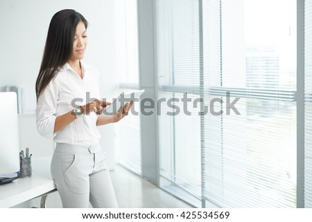Asian business executive using tablet computer in office - stock photo