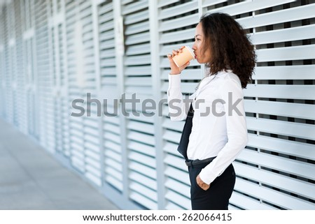 Asian business lady drinking coffee outdoors, side view