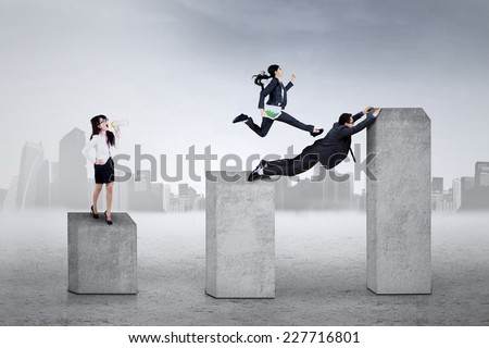Asian business leader giving command to her employees on financial chart - stock photo