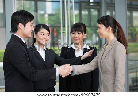 Asian Business man and woman being introduced and shaking hands.
