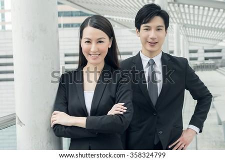 Asian business man and woman in the street, Hong Kong, China. - stock photo