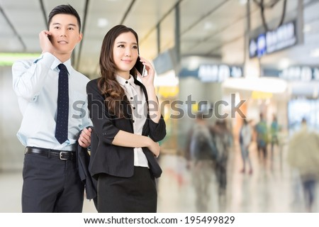 Asian business man and woman talking on cellphone in the station of Hong Kong, Asia.