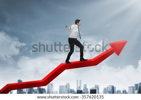 Asian business man balancing increasing arrow chart - stock photo