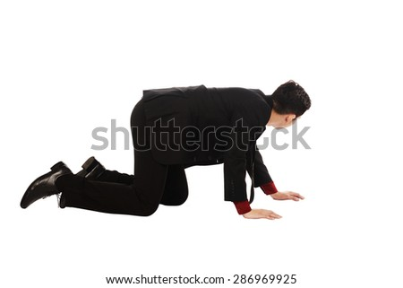 Asian business man crouching isolated over white background - stock photo