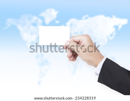 Asian business man hand holding a blank business card over blurred world map of clouds background. - stock photo