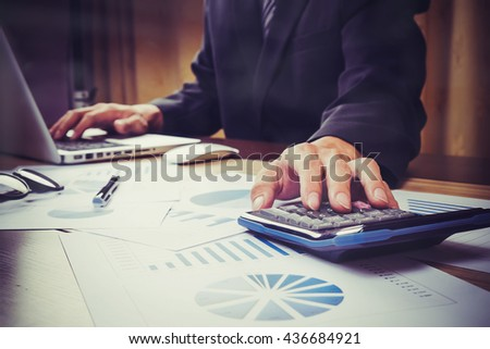 Asian Business man hand pointing at business document during discussion at meeting and using a calculator to calculate the numbers vintage tone - stock photo