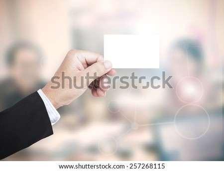 Asian business man hands holding a blank business card over blurred working people in office background. Investment Insurance Agent Trust Thank You Card Friendship CSR Investment Trust concept. - stock photo
