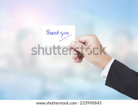 Asian business man holding a handwritten THANK YOU over blurred working people in office background. - stock photo