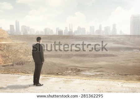 Asian business man looking at the destroyed city. Business corruption conceptual - stock photo
