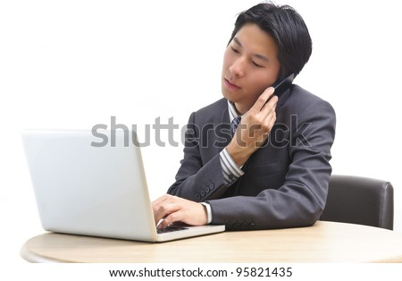 Asian business man on cell phone in front of laptop isolated on white - stock photo