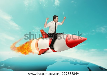 Asian business man riding rocket across the earth - stock photo