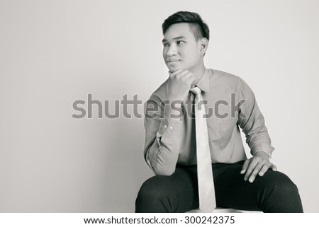 Asian business man sitting on a chair over white background