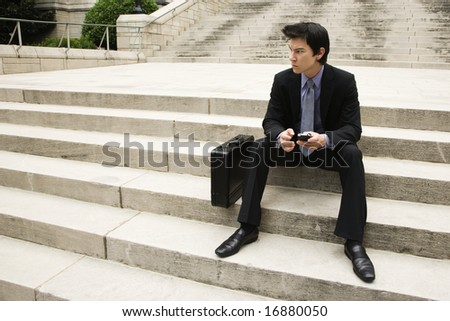 Asian business man sitting on steps in urban area.