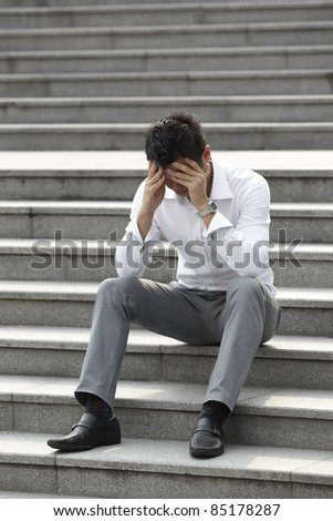 Asian business man sitting steps looking Anxious