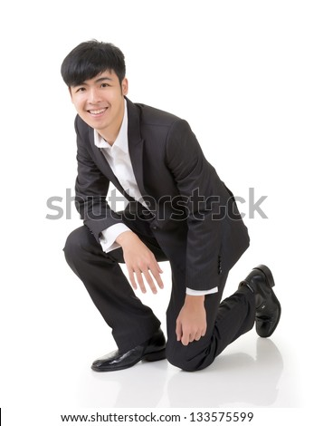 Asian business man squat, full length portrait isolated on white background.