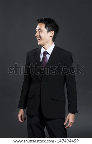 Asian Business man standing and Laughing. Happy Chinese businessman. Dark Background.