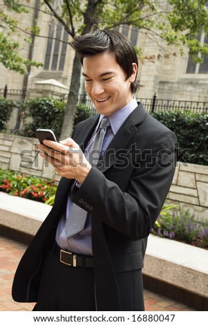 Asian business man standing looking at cell phone messages smiling. - stock photo