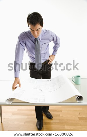 Asian business man standing looking over blueprints.