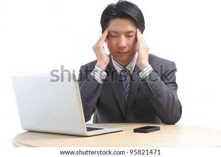 Asian business man suffering from headache and massaging his temples on white background
