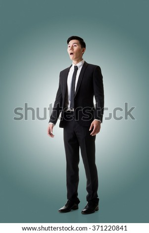 Asian business man surprised with outrageously and funny pose, full length portrait isolated - stock photo