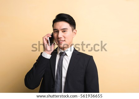 Asian business man talk on phone, closeup portrait on studio yellow background