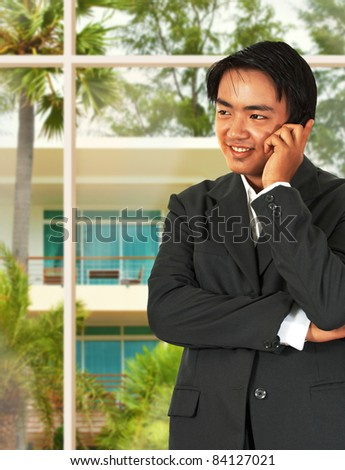 Asian Business Man Talking On The Phone And Standing In His lounge Next To The Garden Window - stock photo