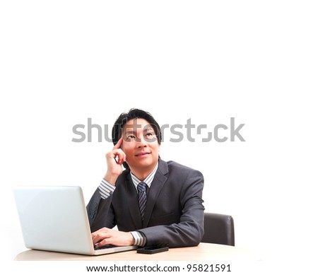 Asian business man thinking in front of laptop isolated on white background - stock photo