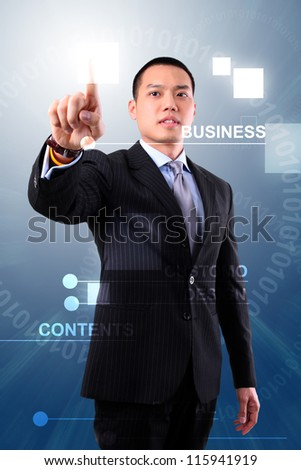 Asian business man touching an imaginary screen or button on visual screen - stock photo