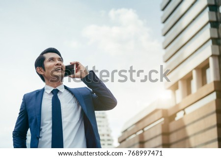 Asian business man use phone talking at outdoor of building