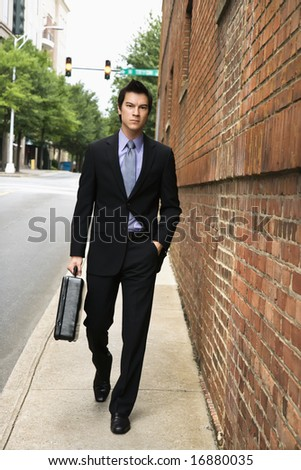 Asian business man walking down sidewalk in the city. - stock photo