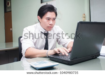 Asian business man working on laptop in office