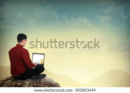 Asian business man working with laptop on the top of the mountain - stock photo