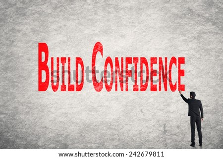 Asian business man write words on wall, Build Confidence - stock photo