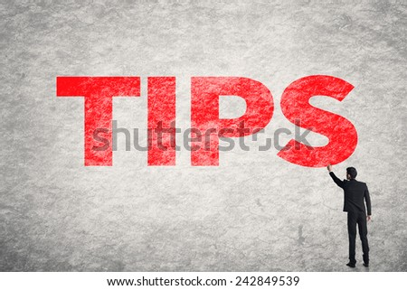 Asian business man write words on wall, Tips - stock photo
