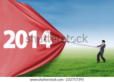 Asian business manager is pulling big number of 2014 outdoor - stock photo