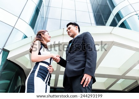 Asian business men and woman outside in front of tower building shaking hands  - stock photo