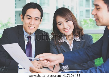 Asian business people discussing document in a meeting - stock photo