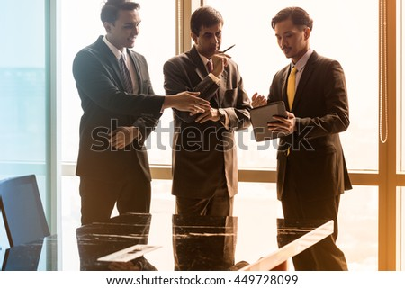 Asian business people having conversation in front of window in conference room, filtered image - stock photo