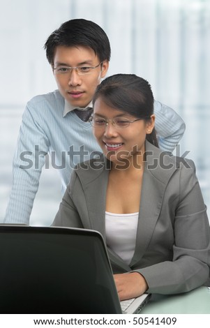 Asian business people looking at laptop in the office